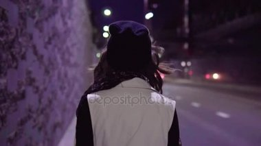 Teenage girl walking along night city street