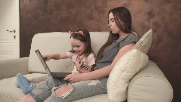 Malá holka ukazuje něco ke své matce na přenosném počítači
