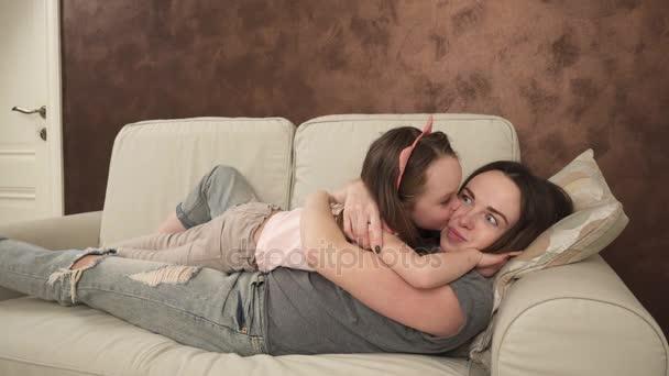 glückliche Mutter und kleine Tochter umarmen und kitzeln