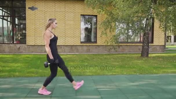 Adult fitness woman doing walking lunges with dumbbells on a sports ground