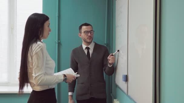 Obchodní muž a žena diskutovat o něco poblíž tabule