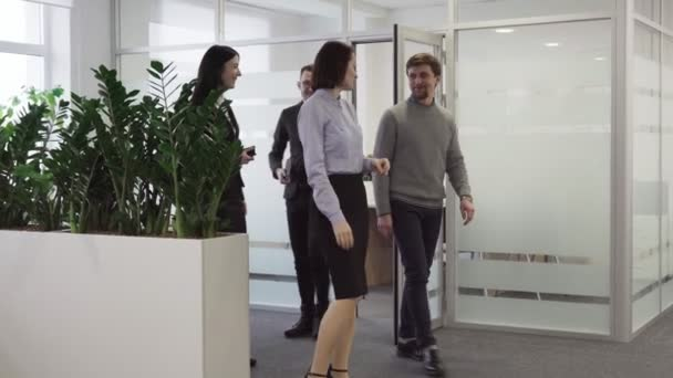Group business people come out of meeting room, smiling and shaking hands