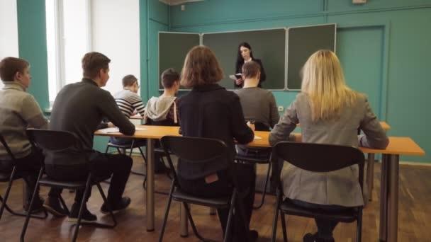 Žena přednášející mluví se studenty ve třídě