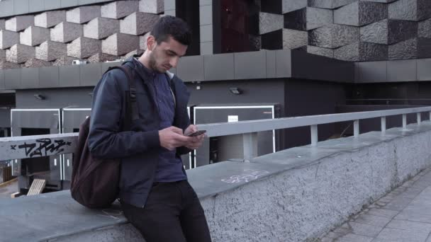 Young handsome arabic man using smartphone in city