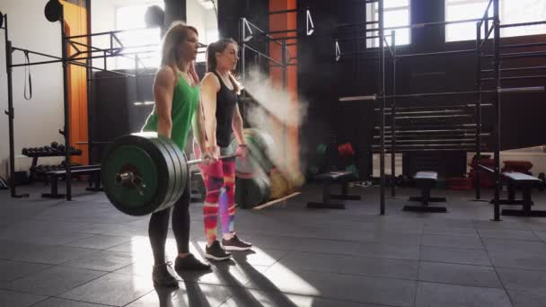 Team of two fitness women doing deadlift workout, giving high five and winning