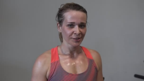 Happy tired sweaty fitness woman showing thumb up gesture during workout in gym
