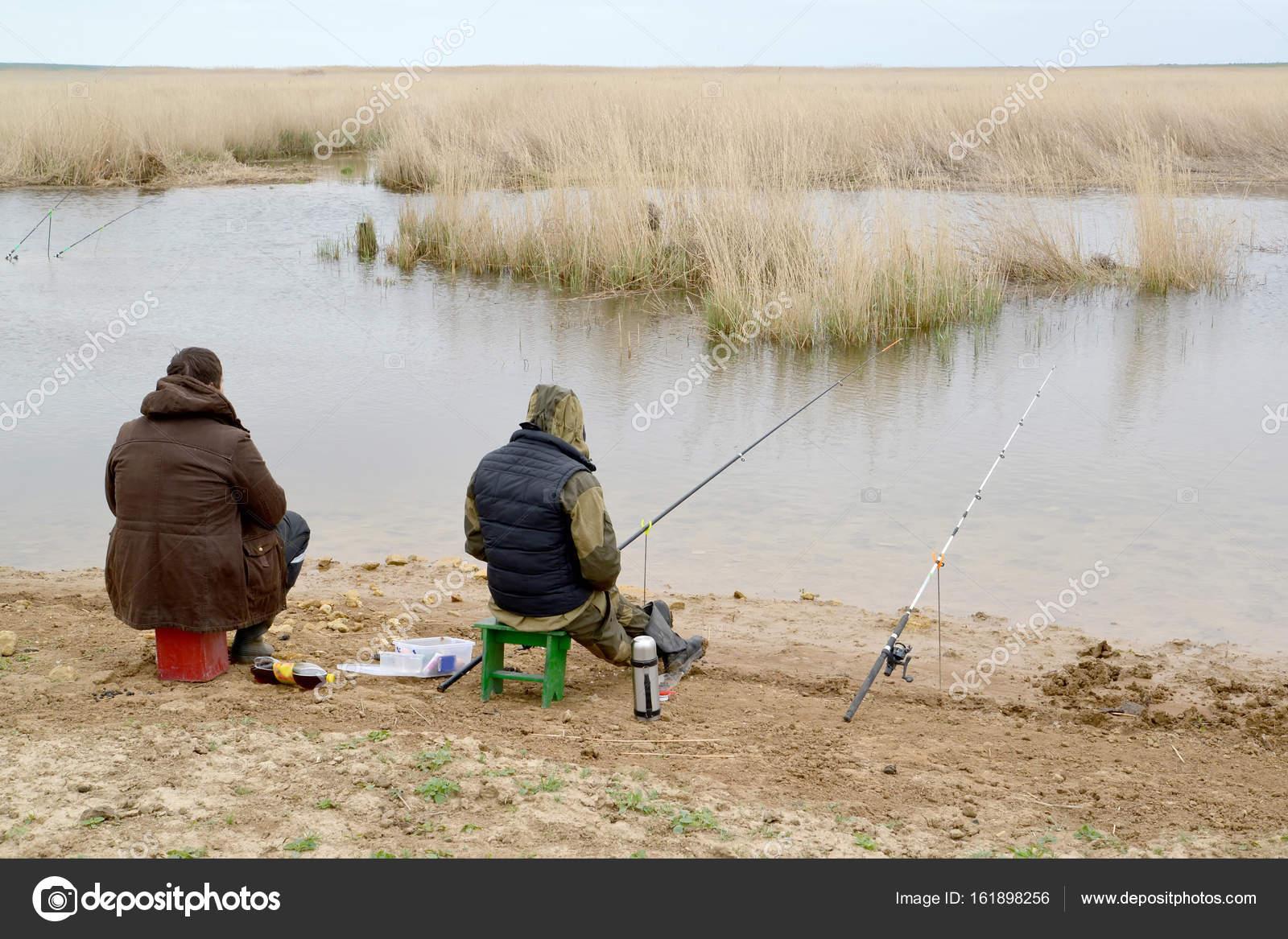 二人の男は、マヌィチ川の魚棒を...
