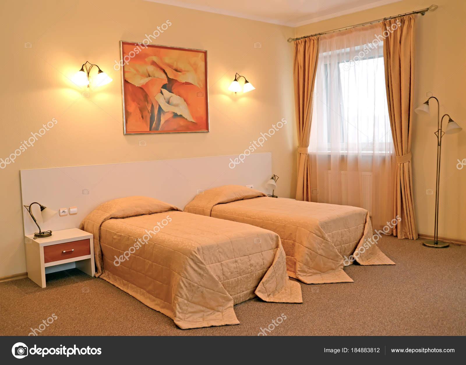 Un interiore di camera da letto con due letti in colori caldi — Foto ...