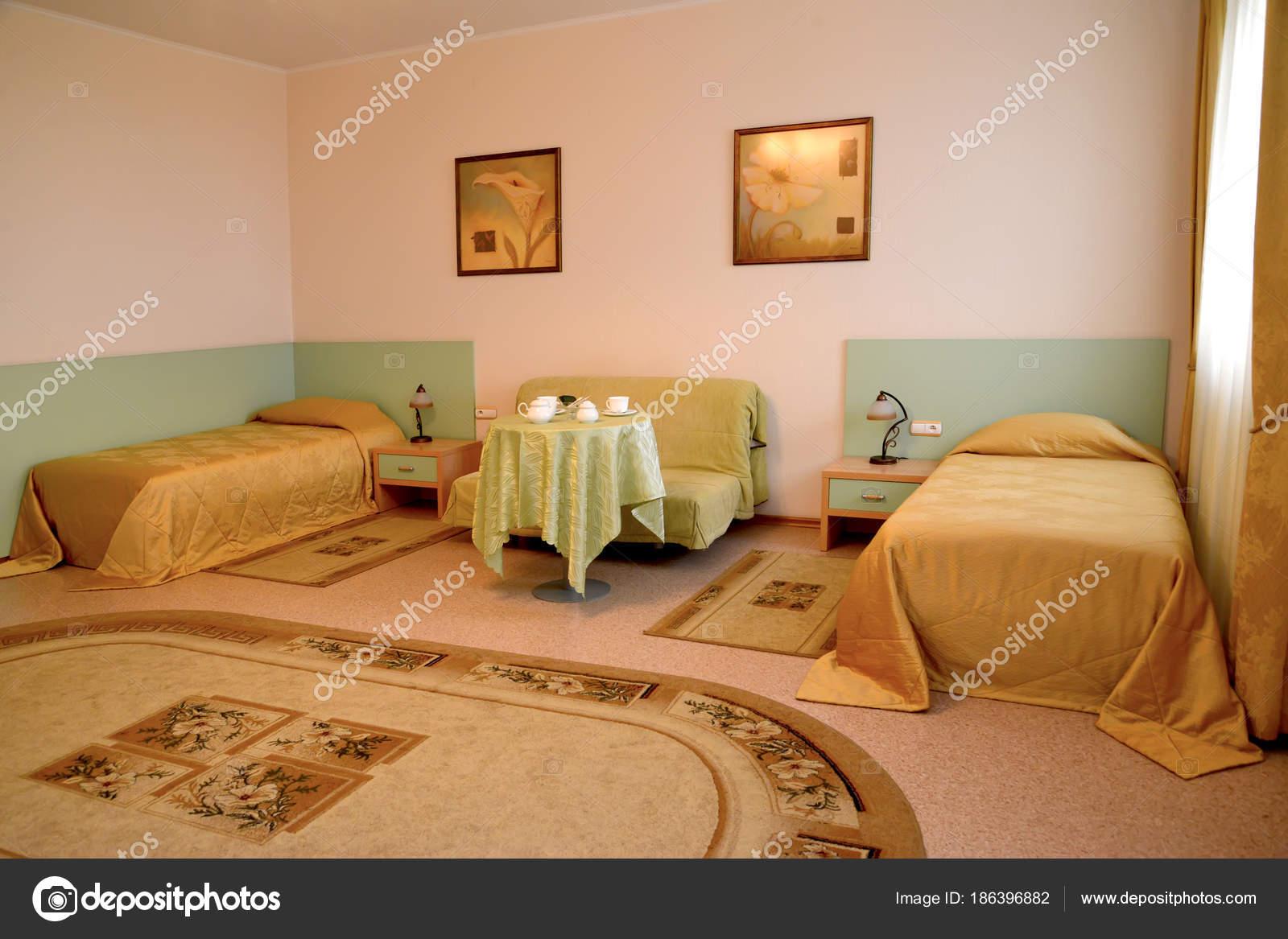 Ein Schlafzimmer-Interieur mit zwei Betten und ein Sofa in warmen ...