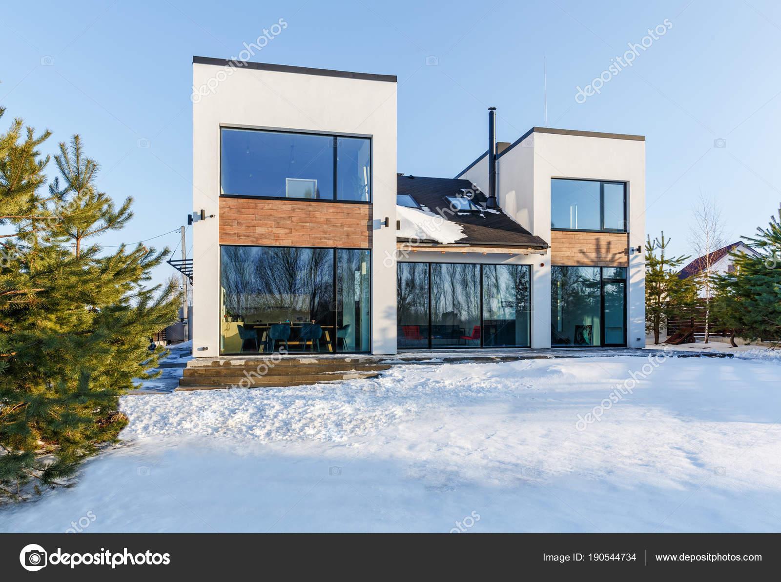 Een modern huis met grote panoramische ramen op de achtergrond van