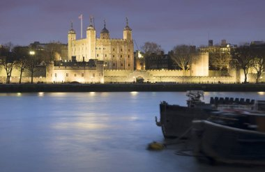 Tower of London at night with river barges in foreground on Rive
