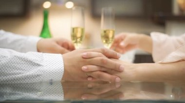 Couple drinking champagne and holding hands.