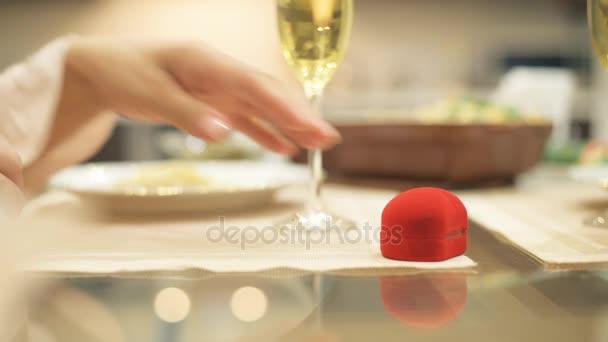 Luomo dà casella rossa con lanello di fidanzamento, rendendo la proposta di matrimonio alla ragazza, chiedendo una mano, allinterno