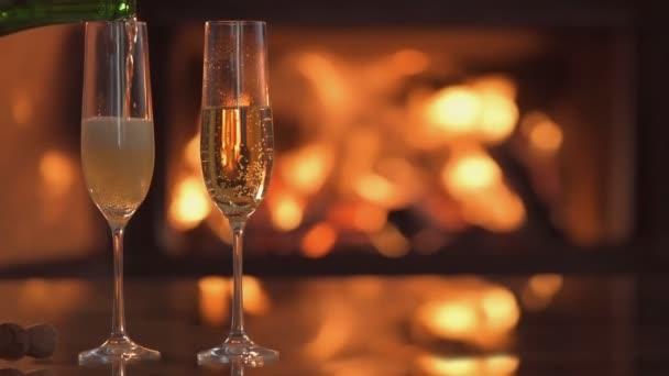 Cinemagraph-šampaňské ve dvě sklenice na stole hořící krb.