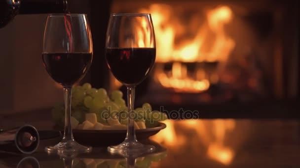 Cinemagraph - egy pohár vörös bor ömlött át kandalló háttér.