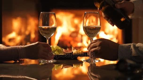 Mladí manželé si romantickou večeři s vínem nad krb pozadí.