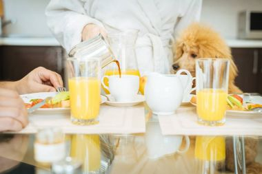 Young woman pours coffee into a cup . Couple having breakfast together.