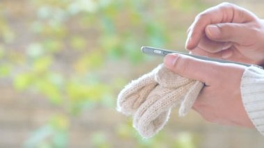 Male hands  using smart phone. Hands hold winter gloves and a smartphone.