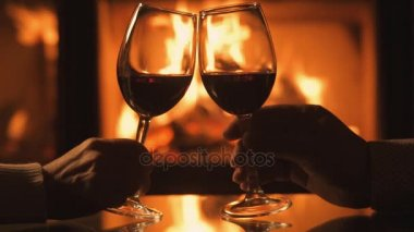 Cinemagraph - Young couple have romantic dinner with wine over fireplace background.