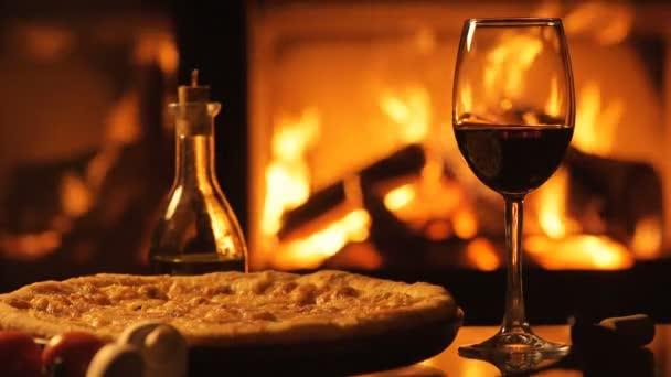 Pizza und ein Rotweinglas über dem Kamin.