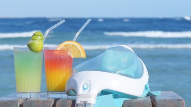 Plavání masku a dva alkoholické koktejly na pozadí moře. Tropická dovolená na pláži.