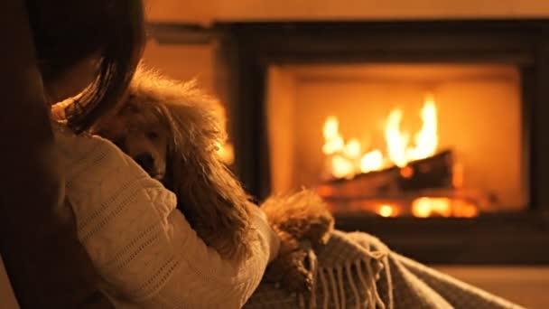 Mladá žena se psem, posezení u krbu