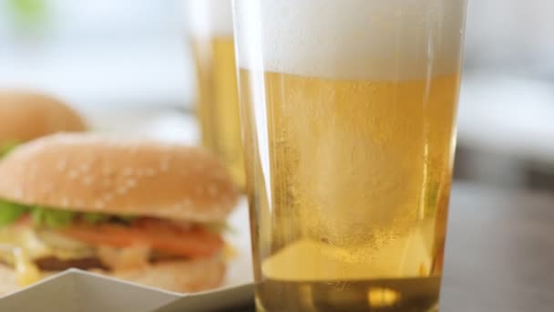 Lití světlé pivo do skla. Dva hamburger s čerstvou zeleninou a pivní sklenice