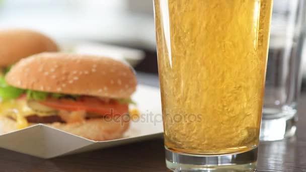 Cinemagraph - nalévání světlé pivo do skla. Dva hamburger s čerstvou zeleninou a pivní sklenice. Pohyb fotografie