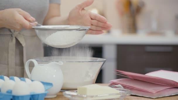 Cinemagraph - žena prosívání mouky přes síto na pečení a na stole leží kniha receptů. Pohyb fotografie