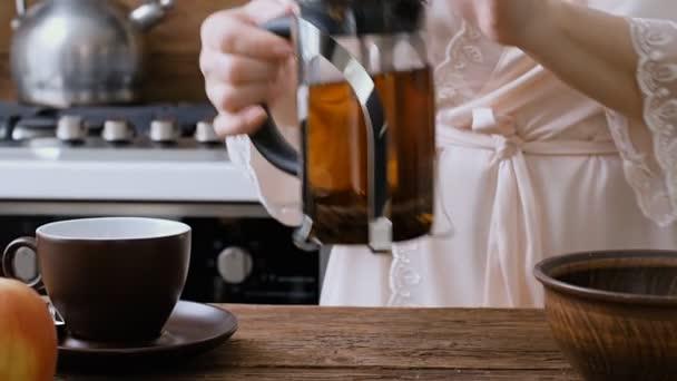 Ženská ruka nalil horký čaj z konvice v poháru.