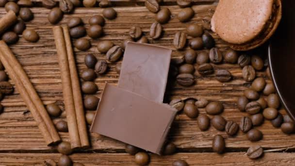 Šálek kávy, fazole, čokoláda a makronky na staré kuchyňském stole. Pohled shora