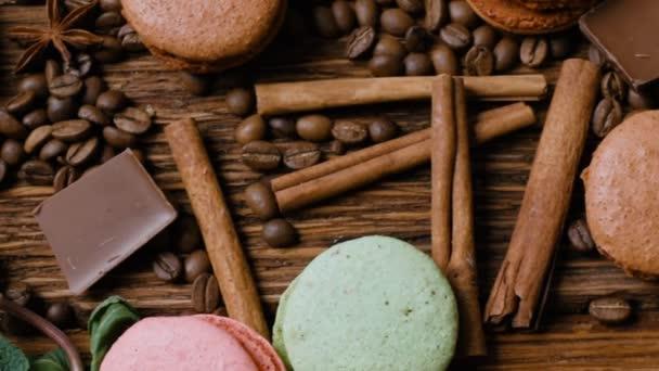 Coffee cup, fazole, čokoláda a barvu makronky na staré kuchyňském stole. Pohled shora