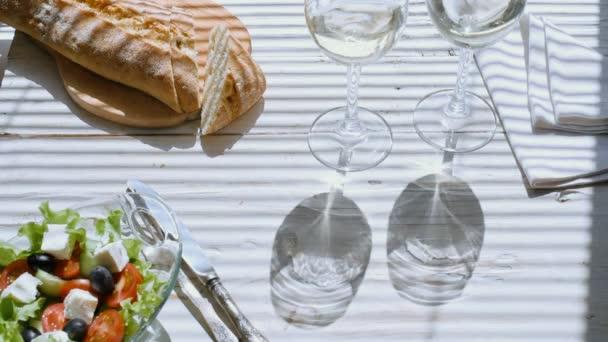 Cinemagraph - Řecký salát a dvě sklenky bílého vína. Pohyb fotografie