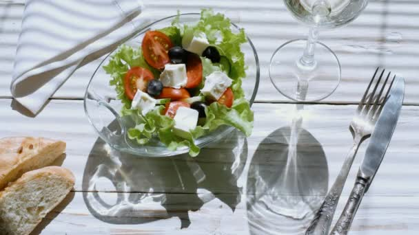 Cinemagraph - Greek salad and a glass of white wine.  Motion Photo.