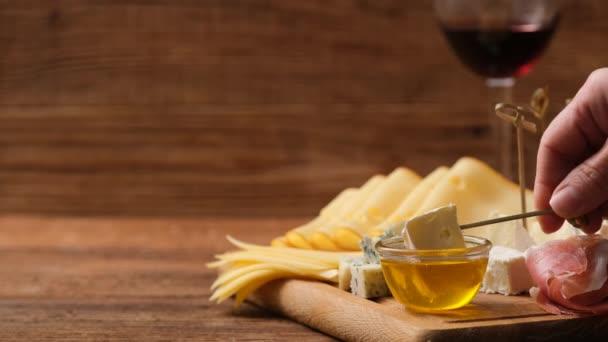Kapky medu kapající s kouskem sýra. Rozmanité sýry na dřevěné desce. Pozadí s prostorem textu.