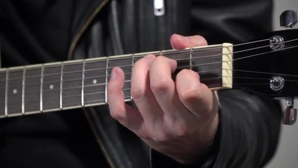 Ein Mann setzt Akkorde, ein großer Schuss. Im Rahmen befinden sich Finger und Finger der Gitarre