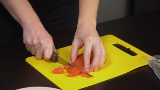 nő vágja hal az asztalon closeup