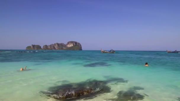 Ao Nang, Thajsko - 24. ledna 2020: Bambusový ostrov je oblíbenou turistickou destinací, takže tradiční dlouhé ocasy lodí sem často přivážejí rekreanty, aby si zaplavali a relaxovali na pláži Bambusu