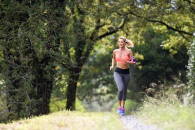 athletic woman running in forest
