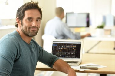 man in office working on laptop