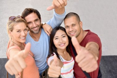 young adults showing thumbs up