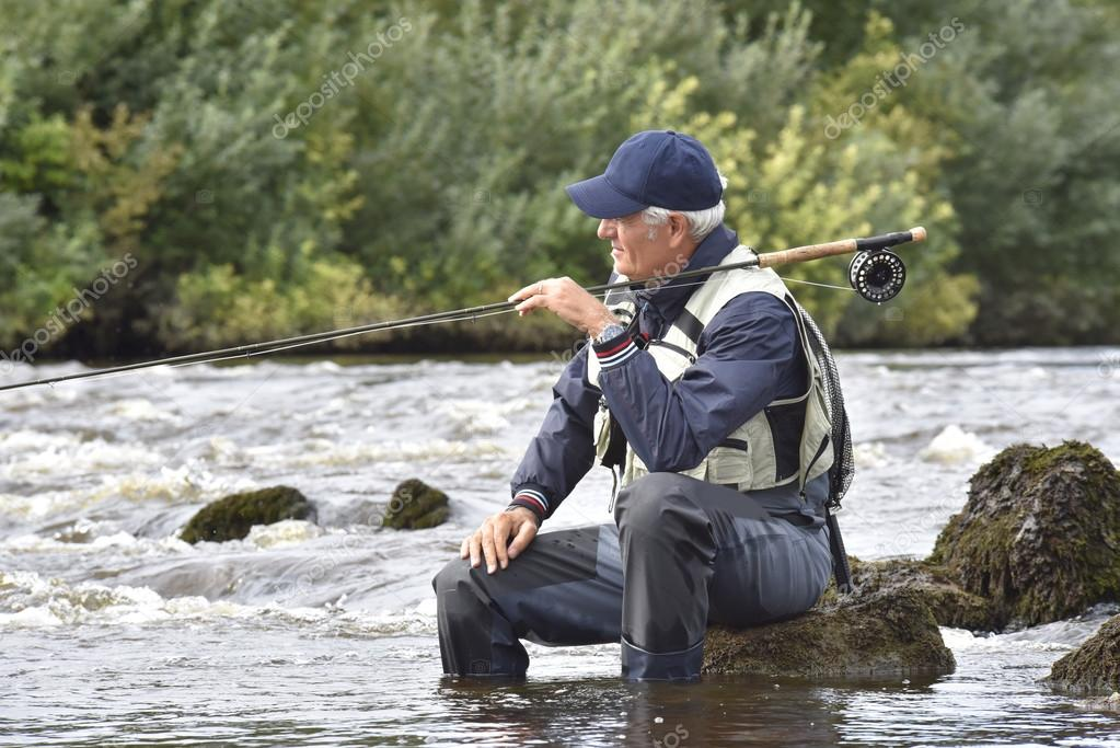 Fly-fisherman waiting with fishing pole