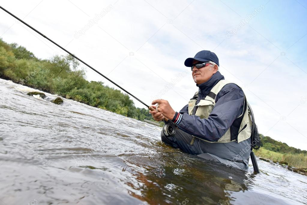 Fly fisherman fishing in river