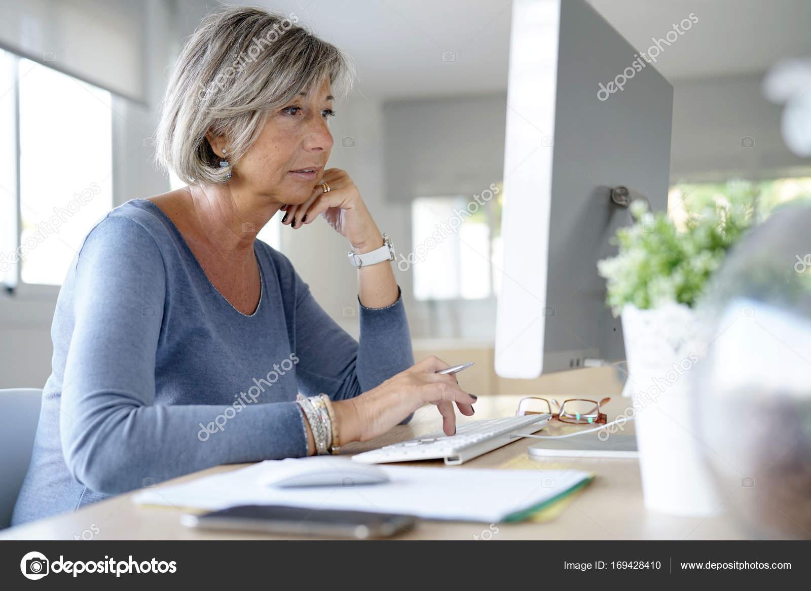 femme travaillant au bureau photographie goodluz 169428410. Black Bedroom Furniture Sets. Home Design Ideas