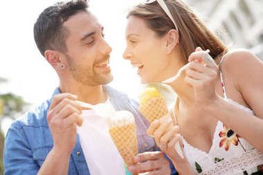 Young couple on vacation eating ice cream
