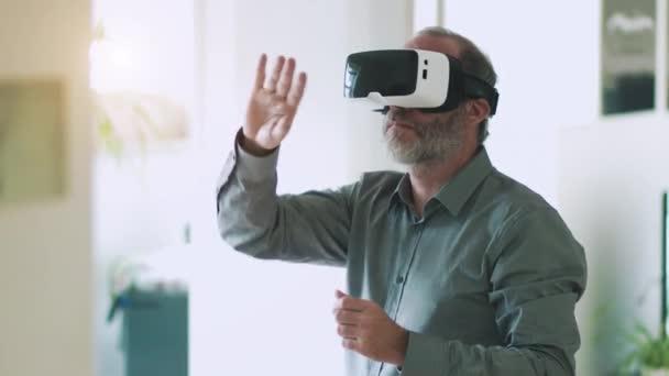 Starší obchodní muž nosí brýle virtuální reality / Vr brýle pro práci v moderní kanceláři