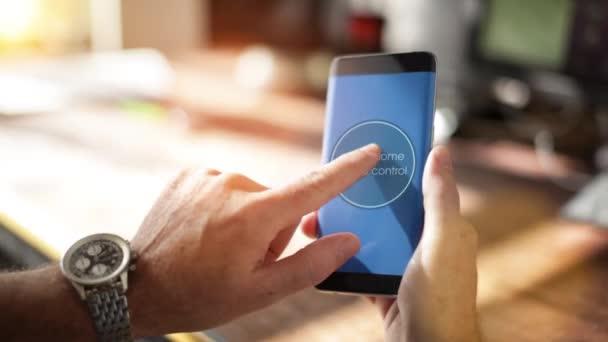 Muž pomocí inteligentních domů aplikace na chytrý telefon