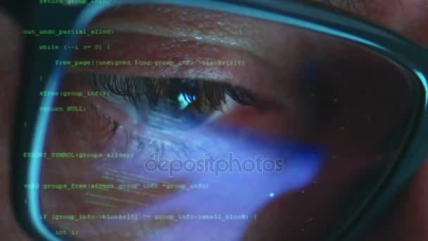 Maschio hacker che lavorano su un computer per cyber attacco mentre verde binario hacking caratteri codice riflettere sul suo volto