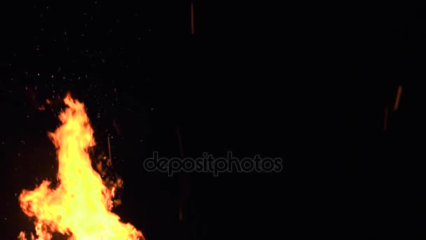 ultra slow motion shot of fire flames and glowing ashes on black background