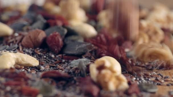 Smíšené Super Foods-zpomaleně padající na dřevěný stůl, zblízka